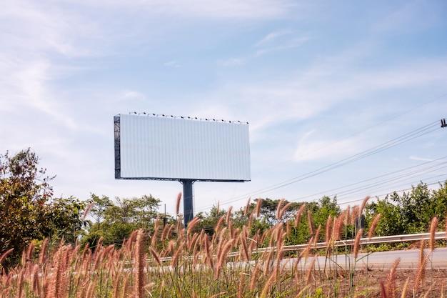 Leere straßenrandanschlagtafel an einem hellen sonnigen tag des blauen himmels mit bereich für ihre mitteilung
