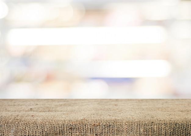 Leere tabelle bedeckt mit sackleinen über unscharfem abstraktem hintergrund mit bokeh
