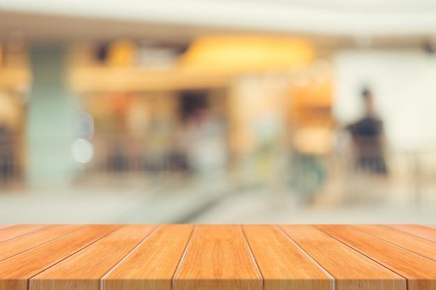 Leere tabelle des hölzernen brettes verwischte hintergrund. braunes holz der perspektive über unschärfe im kaufhaus - kann für anzeige verwendet werden oder ihre produkte montieren. spannen sie oben für anzeige des produktes an.