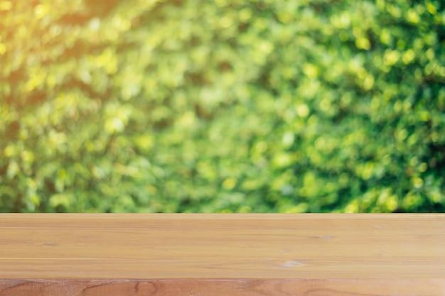 Leere tabelle des hölzernen brettes vor unschärfebäumen im waldhintergrund.