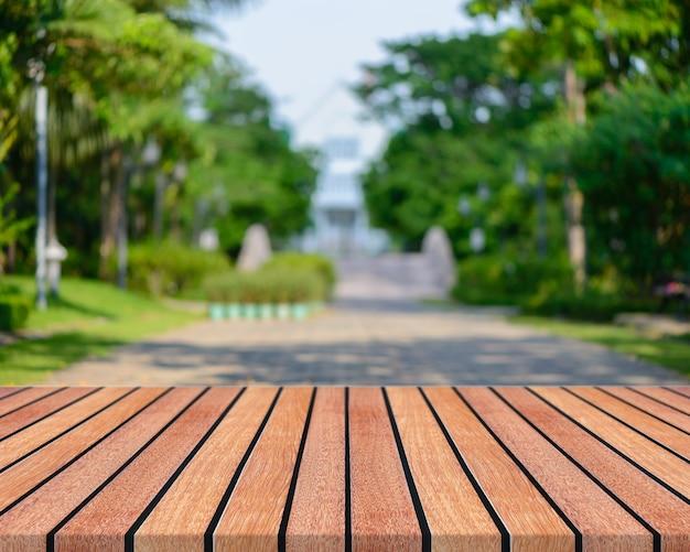 Leere tabelle des hölzernen brettes vor unscharfem hintergrund. braunes holz der perspektive mit unscharfen leuteaktivitäten im park - kann für anzeige verwendet werden oder ihre produkte zusammenbauen. frühling. weinlese gefiltertes bild.
