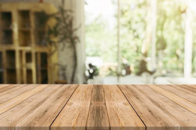 Leere tabelle des hölzernen brettes vor unscharfem hintergrund. braunes holz der perspektive über unschärfe in der kaffeestube - kann für anzeige verwendet werden oder ihre produkte zusammenbauen. spannen sie oben für anzeige des produktes an.