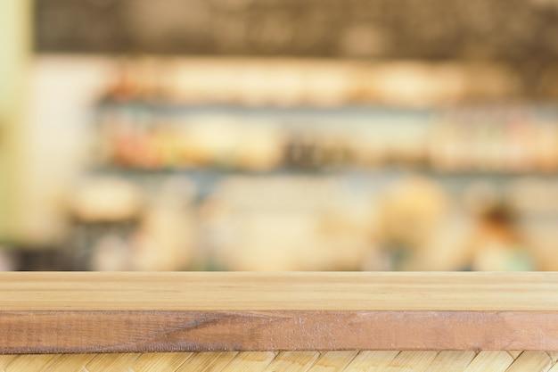Leere tabelle des hölzernen brettes vor unscharfem kaffeestubehintergrund.