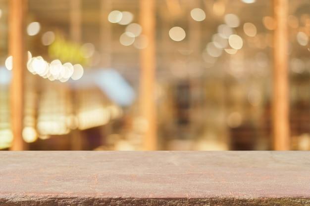 Leere tabelle des steinbrettes vor unscharfem hintergrund. brown-stein der perspektive über unschärfe in der kaffeestube - kann für anzeige oder montagespott herauf ihre produkte verwendet werden. weinlese gefiltertes bild.