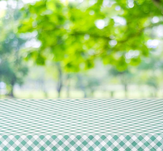 Leere tabelle mit grüner tischdecke über unschärfegarten und bokeh hintergrund, für lebensmittel- und produktanzeigenmontage, frühling und sommersaison
