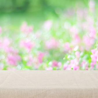 Leere tabelle mit leinentischdecke über unschärfegarten und -blumen