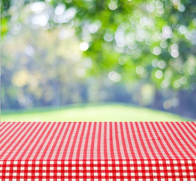 Leere tabelle mit roter und weißer tischdecke über unscharfem hintergrund der parknatur im freien