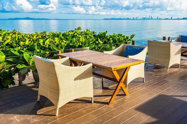 Leere tabelle und stuhl für das speisen des gesetzten fast seeozeanstrandes auf blauem himmel der weißen wolke