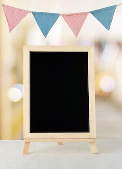 Leere tafel, die über bunten parteiflaggen steht und hintergrund mit kopienraum für text, neues jahr und festivalkarte, fahne verwischt