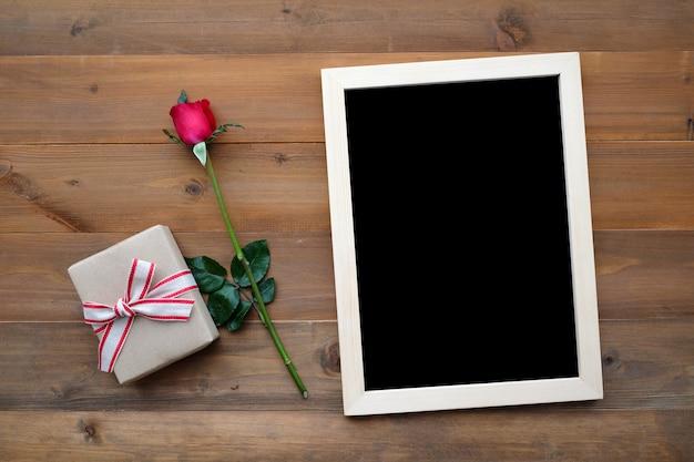 Leere tafel, geschenkbox und rote rose auf holz hintergrund