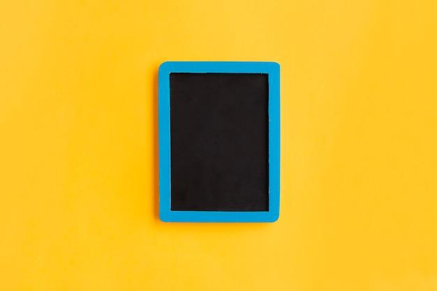 Leere tafel mit blauem holzrahmen auf gelb