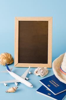 Leere tafel mit dekorativem flugzeug, pässen und muscheln. sommerreisekonzept.