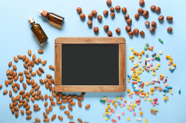 Leere tafel mit gesunden nüssen, pillen und öl auf der farboberfläche