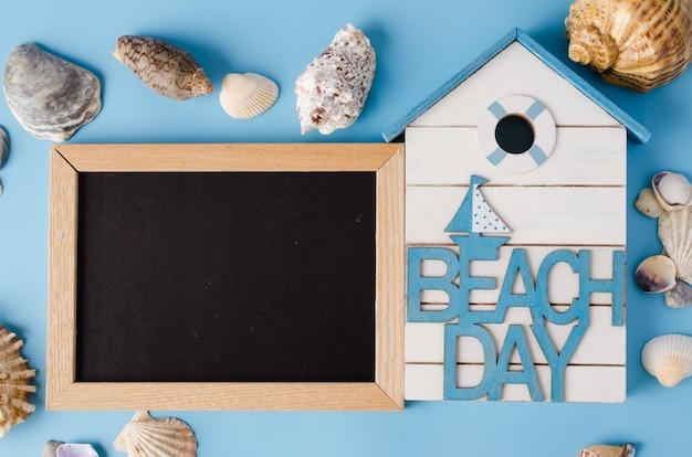 Leere tafel mit muscheln und inschrift strandtag auf blau.