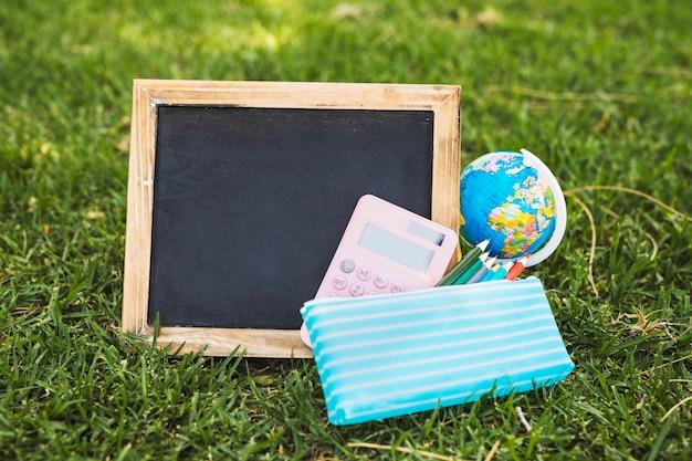 Leere tafel nahe briefpapier und kugel auf gras