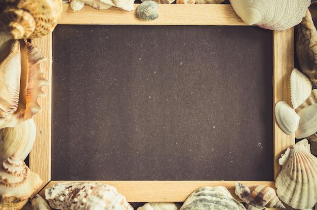 Leere tafel oder fotorahmen mit muscheln.