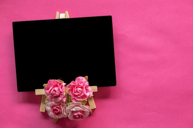 Leere tafel und rosa blume auf rosa hintergrund