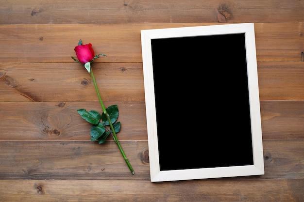 Leere tafel und rote rose auf holz hintergrund
