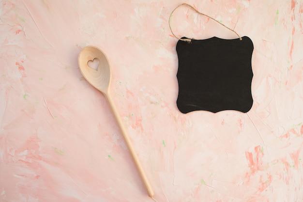 Leere tafel und rührender löffel auf rosa