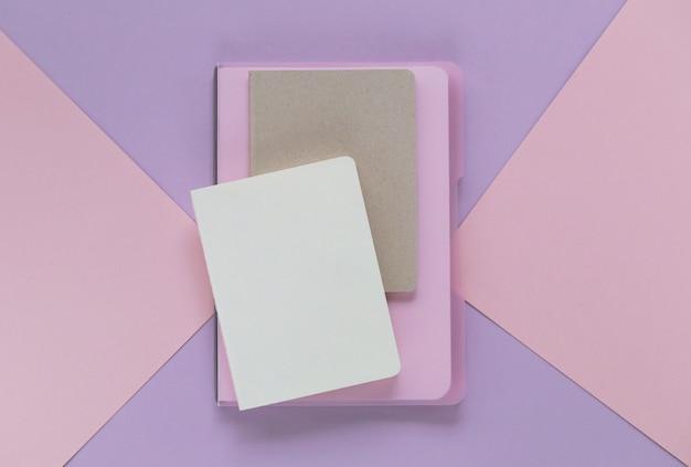 Leere tagebücher auf einem geometrischen hintergrund in den modischen pastelltönen. wohnung lag in pastellfarben. draufsicht, kopie, raum