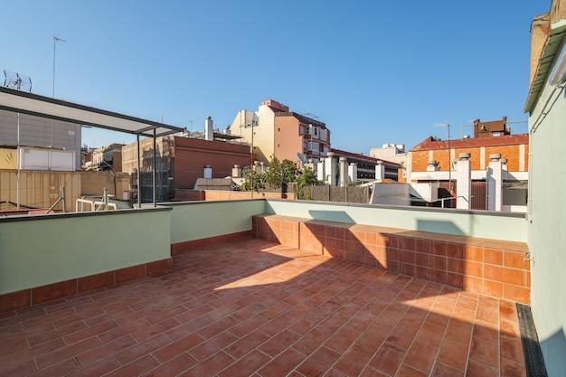 Leere terrasse auf dem dach des modernen gebäudes in barcelona, spanien blick auf die stadt und den blauen himmel auf der sonne...