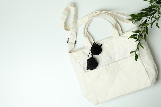Leere textiltasche, zweig und sonnenbrille auf weißem hintergrund