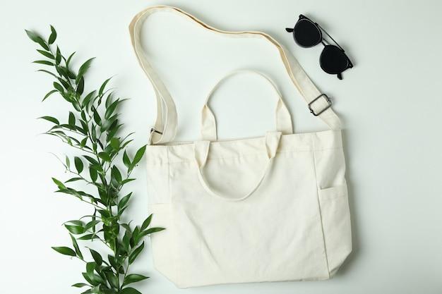 Leere textiltasche, zweig und sonnenbrille
