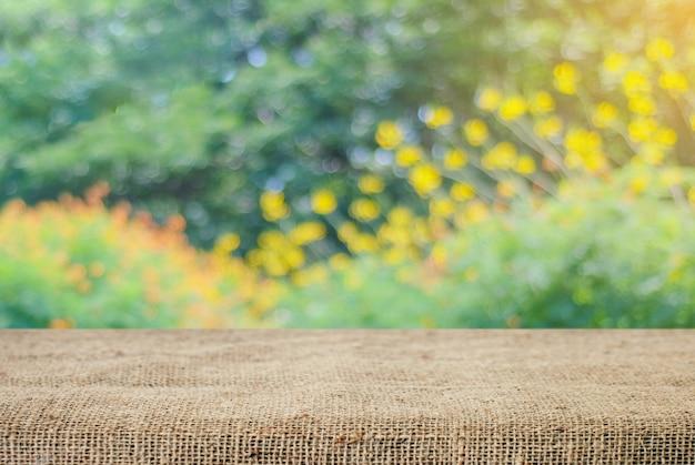 Leere tisch und sack tischdecke über unschärfe baum mit bokeh hintergrund