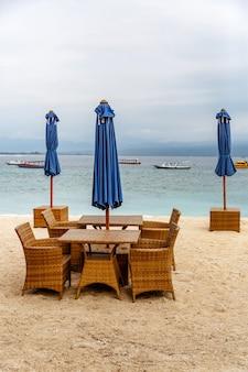 Leere tische des strandcafés. gefaltete regenschirme, mangel an touristen.