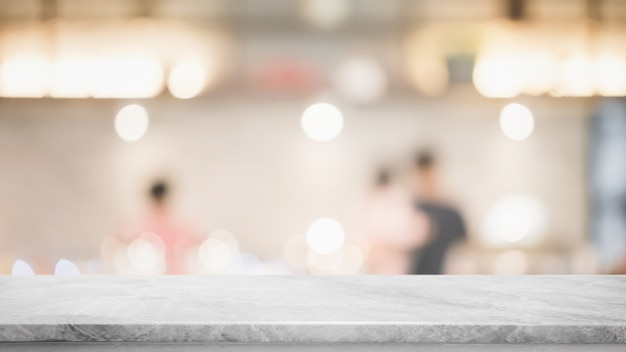 Leere tischplatte aus weißem marmorstein und innencafé mit verschwommenem glasfenster