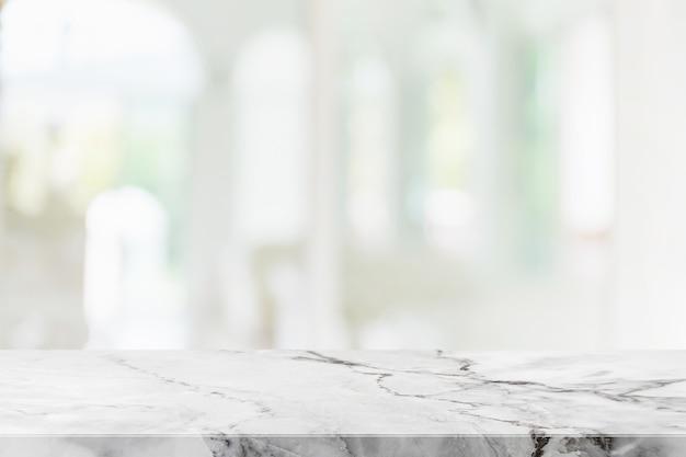 Leere tischplatte aus weißem marmorstein und innenraum aus unscharfem glasfenster