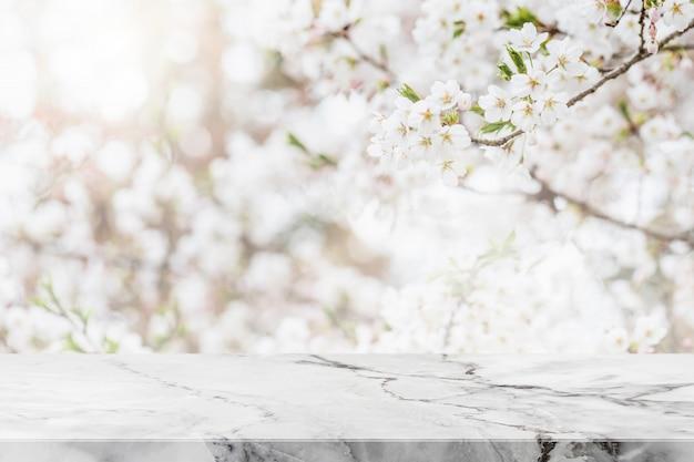 Leere tischplatte aus weißem marmorstein und verschwommener sakura-blumenbaum im gartenhintergrund mit vintage-filter - können zur anzeige oder montage ihrer produkte verwendet werden.