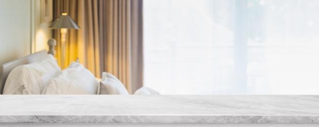 Leere tischplatte aus weißem marmorstein und verschwommenes wohnzimmer im innenraum mit vorhangfenster