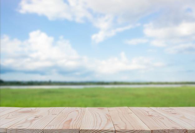 Leere tischplatte des hölzernen brettes an des unscharfen hintergrundes des blauen himmels und des flusses. mit copyspace zur anzeige oder montage ihrer produkte