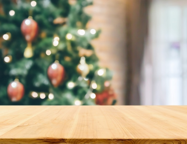 Leere tischplatte mit verschwommenem weihnachtsbaum mit hellem bokeh-hintergrund