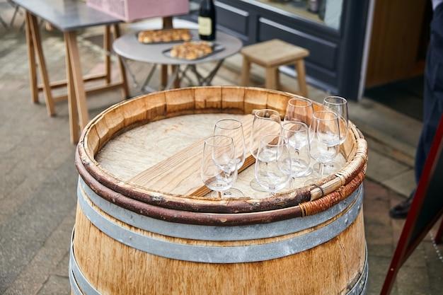 Leere transparente weingläser, die auf einem alten holzfass stehen. straßenweinprobe