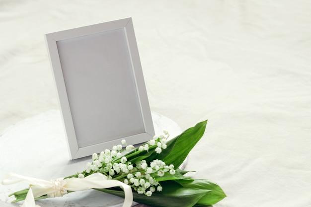 Leere verspotten fotorahmen und bouquet von maiglöckchen