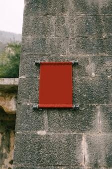Leere vertikale stoffplakette auf einem alten gebäude