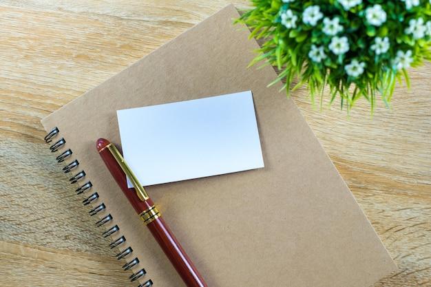Leere visitenkarte oder visitenkarte mit notizbuch auf tabelle