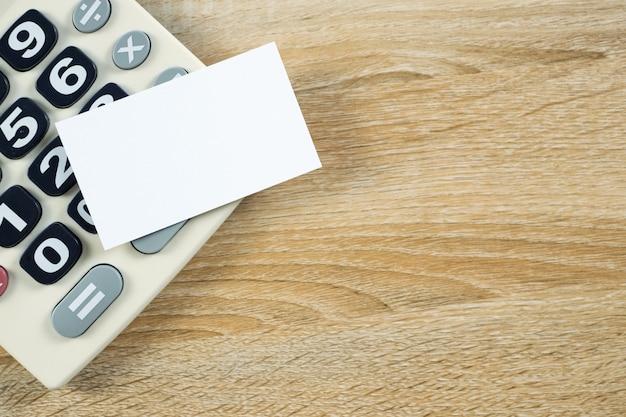 Leere visitenkarte oder visitenkarte mit taschenrechner auf holz