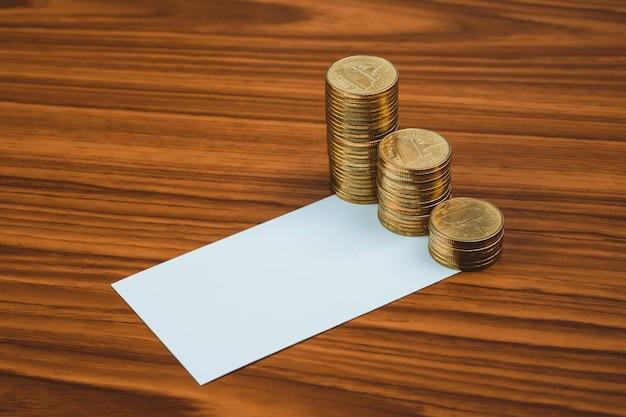 Leere visitenkarte oder visitenkarte und münzenstapel