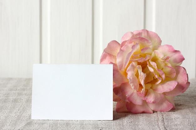 Leere visitenkarte und eine rose auf dem tischmodell mit einem papierkartenhintergrund für ihren text