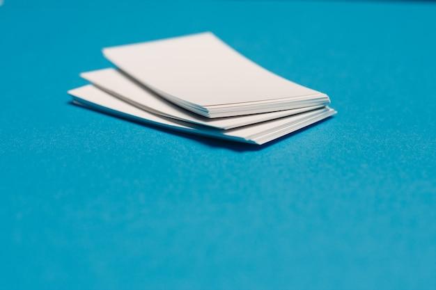 Leere visitenkarten auf schreibtisch hintergrund blau hintergrund stifte mocap