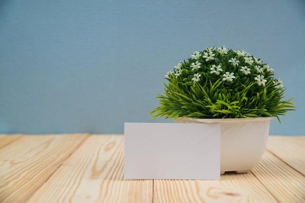 Leere visitenkarten und kleiner dekorativer baum auf holz