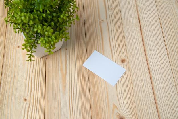 Leere visitenkarten und kleiner dekorativer baum im weißen vase auf hölzernem arbeitstisch