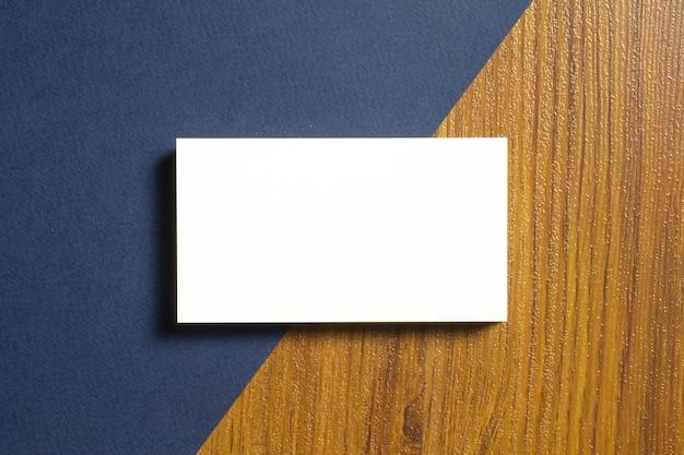 Leere visitenkarten zur hälfte liegen auf blau strukturiertem papier und holzschreibtisch