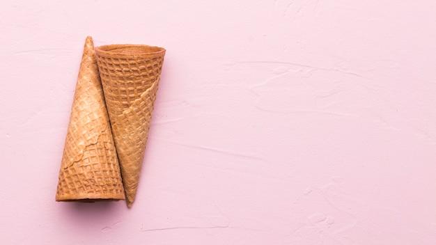 Leere waffelkegel auf rosa hintergrund