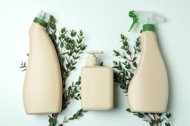 Leere waschmittelflaschen und zweige auf weißem isoliertem hintergrund