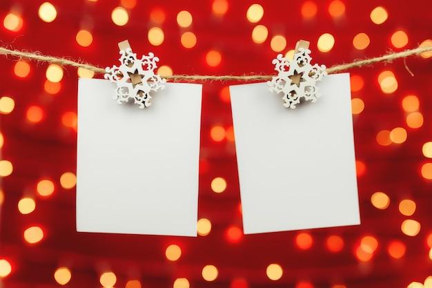 Leere weihnachtsgrußkarte, die an weinlesewäscheleine hängt