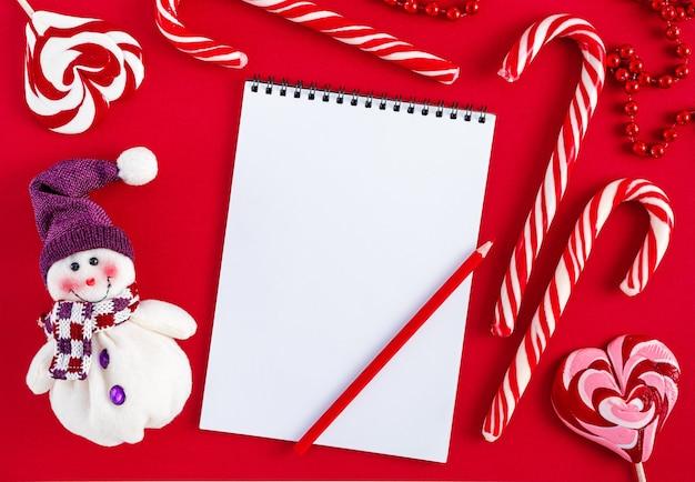 Leere weihnachtswunschliste leer mit süßigkeiten und schneemann auf rotem hintergrund